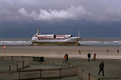 """BLANKENBERGE, BELGIUM - NOVEMBER 9, 2001 -  The German cargo ship """"Heinrich Behrmann"""", was beached by heavy seas after losing power to the main engine late Thursday night at Blankenberge. The ship was heading for the port at Zeebrugge from Ireland, and was carrying dry cargo, none of which was hazardous. The salvage company Unie Van Redding - En Sleepdienst N.V. was hired to free the ship. Three unsuccessful attempts were made Friday, the second attempt resulted in the injury of two workers when tug boat cables snapped. The beached ship has attracted the attention of curious tourists. (Photo © Jock Fistick)"""