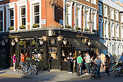 Family group passing customers enjoying warm weather at The Princess traditional London pub in Chalcot Road, Primrose Hill, London