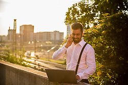 Businessman working on laptop with talking on mobile phone at sunset, Munich, Bavaria, Germany