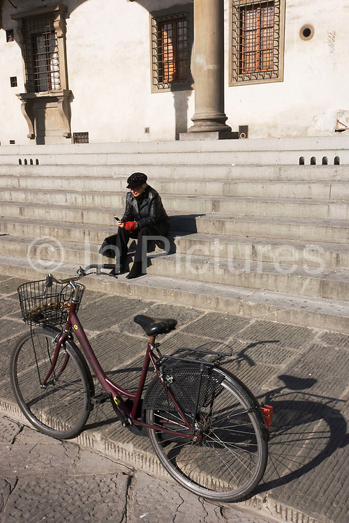 A local woman uses her mobile phone while sitting on steps near her bicycle of a public building in Florence's Piazza Di Annunziata. There is little colour in this image of history and urban decay but there is a peace and stillness amid an otherwise busy metropolis. Many citizens of this once-grand renaissance cultural capital use the moped and scooter and of course, the bike as urban transport though this form of transportation is particularly uncomfortable as the old stones in roads and pavements are rutted and very rough.