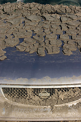 30 Sept, 2005.  New Orleans, Louisiana. Lower 9th ward. Hurricane Katrina aftermath. <br /> The remnants of the lives of ordinary folks, now covered in mud as the flood waters remain. Mud dried to the hood of this Nissan.<br /> Photo; ©Charlie Varley/varleypix.com