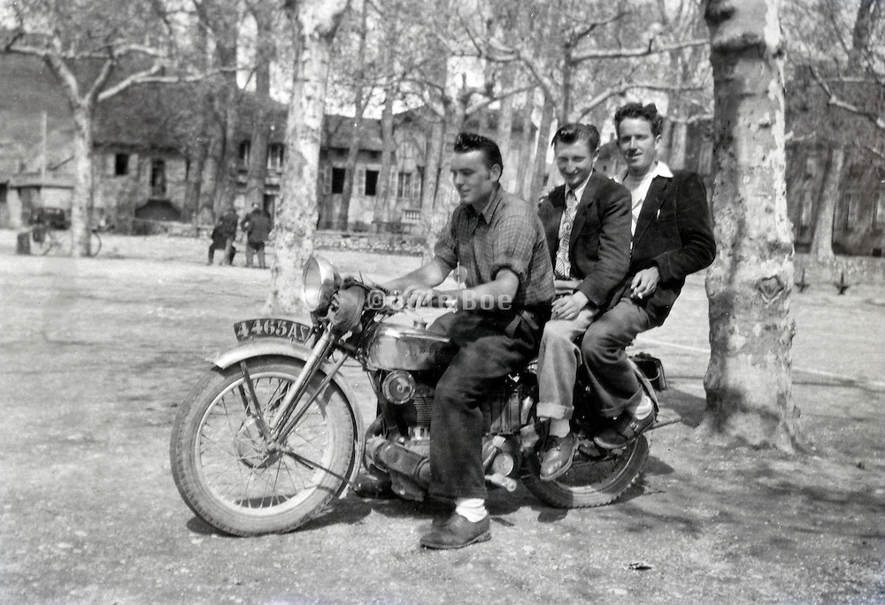 three young adult boys sitting on a motorcycle rural France