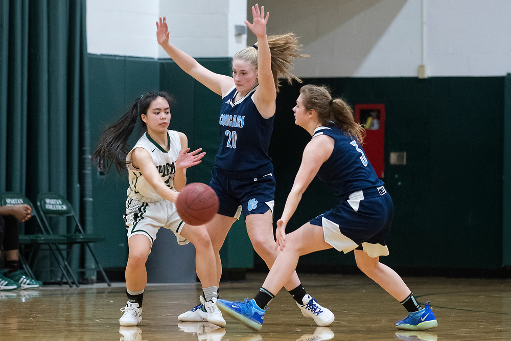 MMU's Meadow Worthley (20) and Caitlyn Luitjens (3) guard Winooski's Penny Ly (4) during the girls basketball game between the Mount Mansfield Cougars and the Winooski Spartans at Winooski High School on Friday night February 14, 2020 in Winooski, Vermont.(BRIAN JENKINS/for the FREE PRESS)