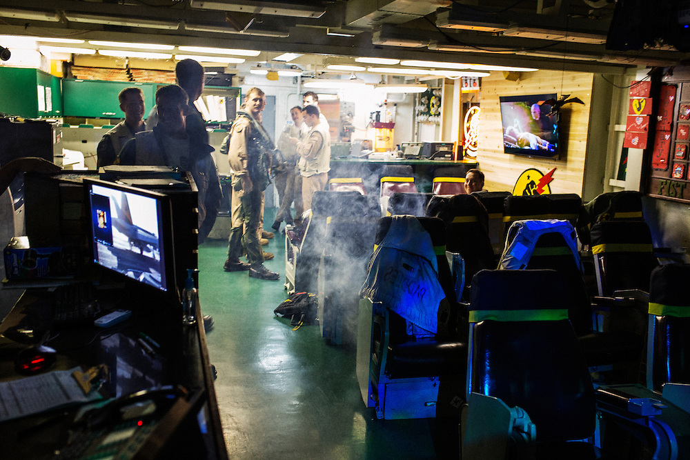"""Inside the ready room of  VFA-25, a strike fighter squadron that is known in the Navy as """"Fist of the Fleet"""". Landing Safety Officers were visiting the squadron to report on the grades of pilots' landings. To celebrate, the squadron fired some smoke and played music.<br /> <br /> Aboard the USS Harry S. Truman operating in the Persian Gulf. February 25, 2016.<br /> <br /> Matt Lutton / Boreal Collective for Mashable"""
