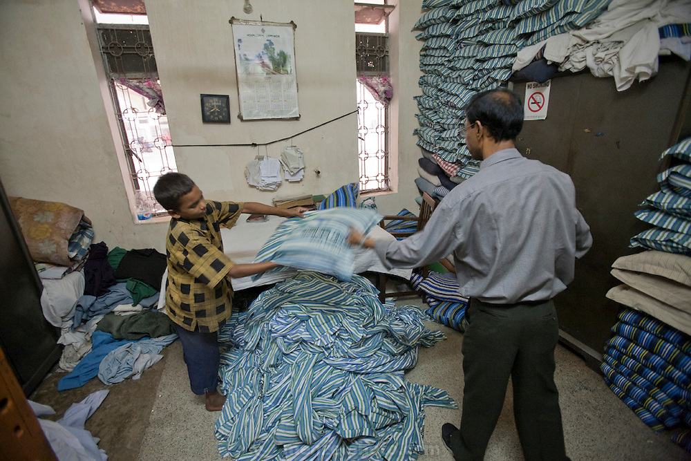 Alamin Hasan helps with train bedding from the sleeper cars at the Kamalapur Railway Station in Dhaka, Bangladesh, where he works as a porter. (Featured in the book What I Eat: Around the World in 80 Diets.) MODEL RELEASED.