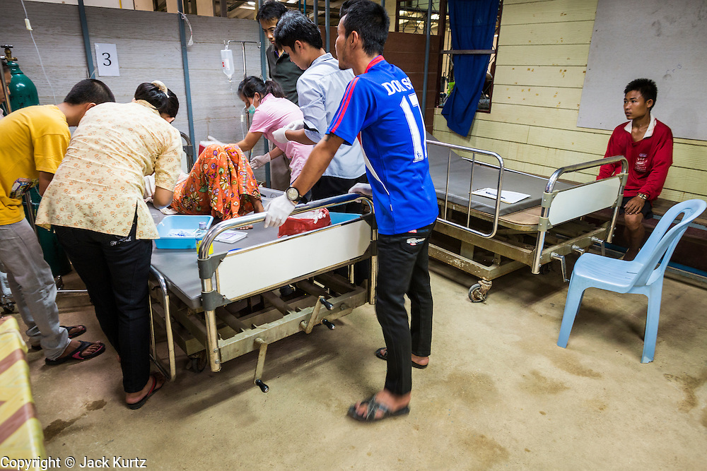 20 MAY 2013 - MAE KASA, TAK, THAILAND:  A man (FAR RIGHT) watches as health care workers help his wife, who had gone into shock because of an etopic pregnancy, in the SMRU clinic intensive care room at the Mae Kasa clinic. Health professionals are seeing increasing evidence of malaria resistant to artemisinin coming out of the jungles of Southeast Asia. Artemisinin has been the first choice for battling malaria in Southeast Asia for 20 years. In recent years though,  health care workers in Cambodia and Myanmar (Burma) are seeing signs that the malaria parasite is becoming resistant to artemisinin. Scientists who study malaria are concerned that history could repeat itself because chloroquine, an effective malaria treatment until the 1990s, first lost its effectiveness in Cambodia and Burma before spreading to Africa, which led to a spike in deaths there. Doctors at the Shaklo Malaria Research Unit (SMRU), which studies malaria along the Thai Burma border, are worried that artemisinin resistance is growing at a rapid pace. Dr. Aung Pyae Phyo, a Burmese physician at a SMRU clinic just a few meters from the Burmese border, said that in 2009, 90 percent of patients were cured with artemisinin, but in 2010, it dropped to about 70 percent and is now between 55 and 60 percent. He said the concern is that as it becomes more difficult to clear the parasite from a patient, progress that has been made in combating malaria will be lost and the disease could make a comeback in Southeast Asia.    PHOTO BY JACK KURTZ