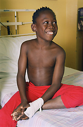 Young patient with bandaged hand sitting on bed on Children's medical ward smiling,