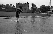 """Flooding at the Dodder..1986..26.08.1986..08.26.1986..28th August 1986..As a result of Hurricane Charly (Charlie) heavy overnight rainfall was the cause of severe flooding in the Donnybrook/Ballsbridge areas of Dublin. In a period of just 12 hours it was stated that 8 inches of rain had fallen. The Dodder,long regarded as a """"Flashy"""" river, burst its banks and caused great hardship to families in the 300 or so homes which were flooded. Council workers and the Fire Brigades did their best to try and alleviate some of the problems by removing debris and pumping out some of the homes affected..Note: """"Flashy"""" is a term given to a river which is prone to flooding as a result of heavy or sustained rainfall...Image of a pedestrian braving the elements as he crosses a flooded street. Gum boots or wellingtons were essential."""