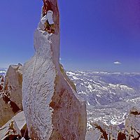 A mountaineer stands atop 14,040+ foot Starlight Peak, on the Palisade Crest in California's Sierra Nevada.  This summit divides Kings Canyon National Park (background) and John Muir Wilderness.