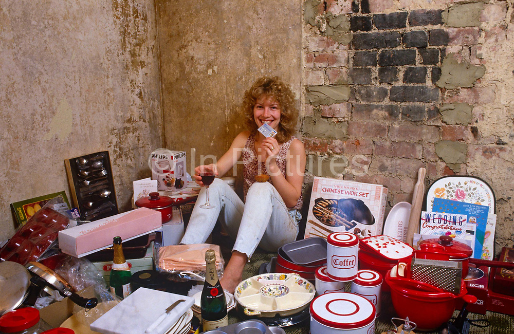 A housewife poses in her still undecorated home surrounded by material possessions bought with a credit card during the must-have economy. Shot in an era of Thatcherite must-have materialism, when the credit economy was a way of life for millions, decades before the recessions and financial crashes of the Noughties, this lady holds up her Visa card and glass of red wine. Surrounded by her purchases bought on credit, she smiles at us with economic confidence.