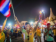"""05 MAY 2104 - BANGKOK, THAILAND:  A man carrying a Thai flag shouts """"Long Live the King"""" during candlelight vigil for Bhumibol Adulyadej, the King of Thailand, on Ratchadamnoen Ave in front of Sanam Luang in Bangkok. Thousands of Thais packed the area around Sanam Luang and the Grand Palace Monday evening for a special ceremony to mark Coronation Day, which honored the 64th anniversary of the coronation of Bhumibol Adulyadej, the King of Thailand. Many of the people also support the anti-government movement led by Suthep Thaugsuban. Most of the anti-government protesters are conservative supporters of the monarchy.   PHOTO BY JACK KURTZ"""