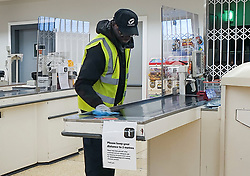 © Licensed to London News Pictures. 30/03/2020. London, UK. A cleaner cleans the checkout, recently protected with a Perspex guard at a Sainsbury's supermarket in north London as coronavirus lockdown continues. Photo credit: Dinendra Haria/LNP