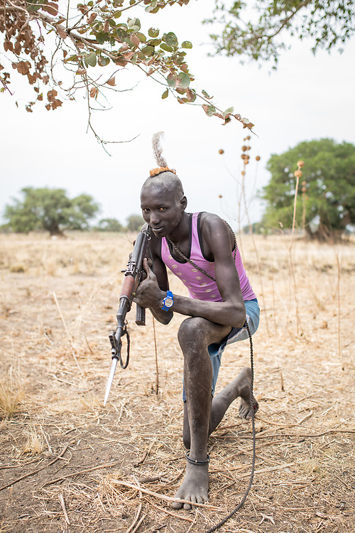 """Matoch joined the vaccination site with his ten cows. """"Our cattle is all we have. If someone tries to steal one of my cows, I will fight. This is why I always move around with my weapon"""". South Sudan, 2020."""
