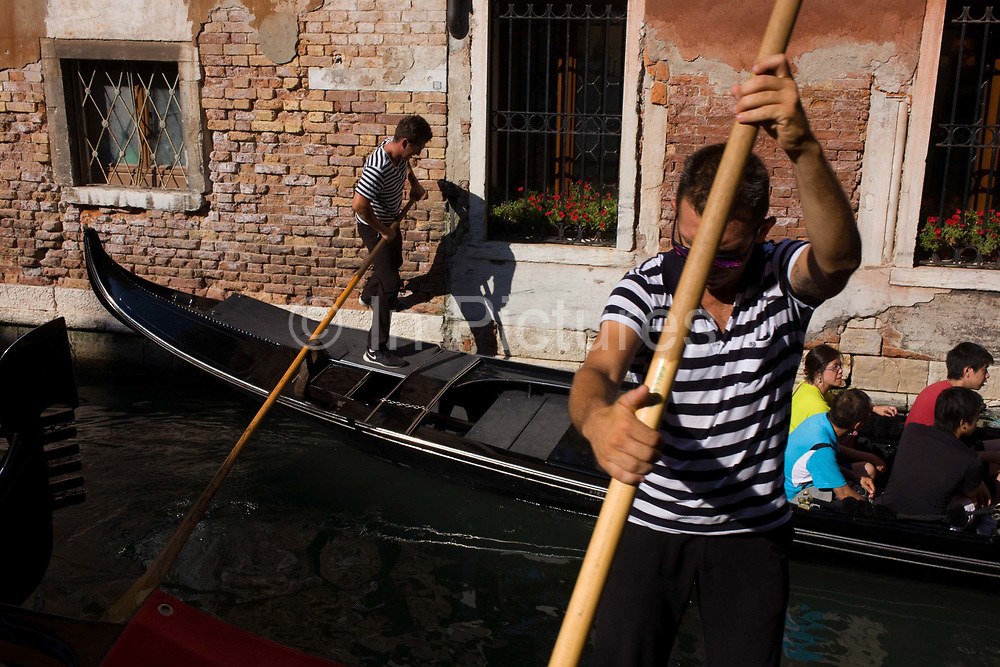 A gondolier kicks against a wall to straighten his gondola during a ride in a narrow canal in Venice, Italy. The first mention ever of an Italian gondola was in Venice in 1094 and, of course, there have been gondoliers as long as there have been gondolas - so it's one of the oldest professions in the world. Until August 2010, there had never been a single woman gondolier in Venice as licences were always passed down to male family members. Current prices (2015) is 80 Euros for a 40-minute journey (earning them approx 130,000 Euros a year) along the waterways of this old city but rarely do gondoliers wear their straw hat.