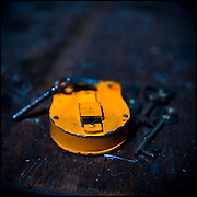 A yellow padlock with keys on a wooden table, shot in an abandoned mental asylum.