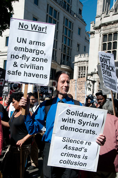 Demonstration against any intervention in Syria called by Stop the War and CND, August 30th 2013, Central London. Peter Tatchell, political activist, holds placards saying 'No war, UN arms embargo, no-fly zone and civilian safe havens' and 'Solidarity with Syrian democrats. Silence re Assad's crimes is collusion'.