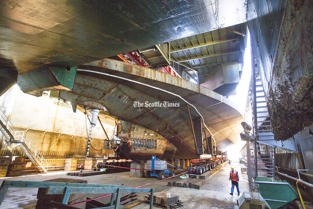 A worker walks beneath the hull of the Chimacum, the newest state ferry, under final assembly at Vigor Shipyard in Seattle. (Mike Siegel / The Seattle Times)