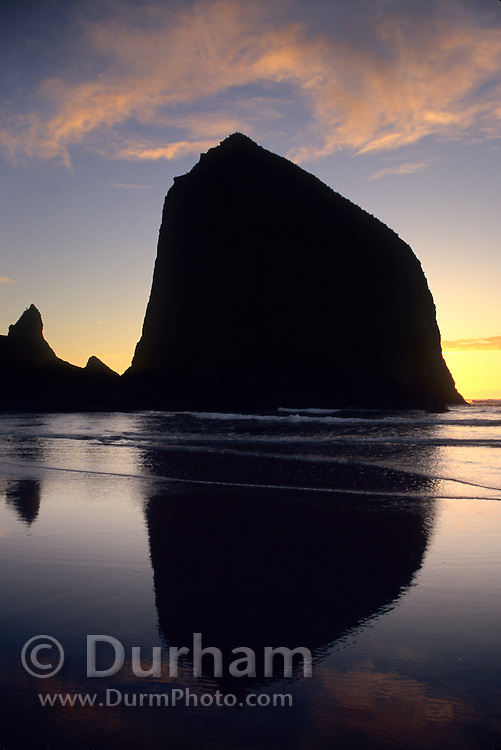 A series of irregular basalt rock projections along Cannon Beach on the Oregon Coast. The largest is known as Haystack Rock. Seen in silhouette at sunset.
