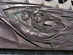 Detail of communist era patriotic steel sculpture on facade of office tower at Alexanderplatz in former East Berlin Germany