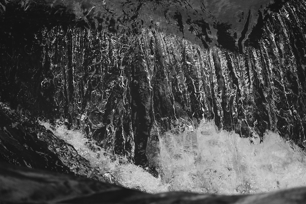 Water descending over the edge of Warren Falls on a summer morning.