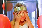 Young girl of 4 with closed eyes making her birthday wish