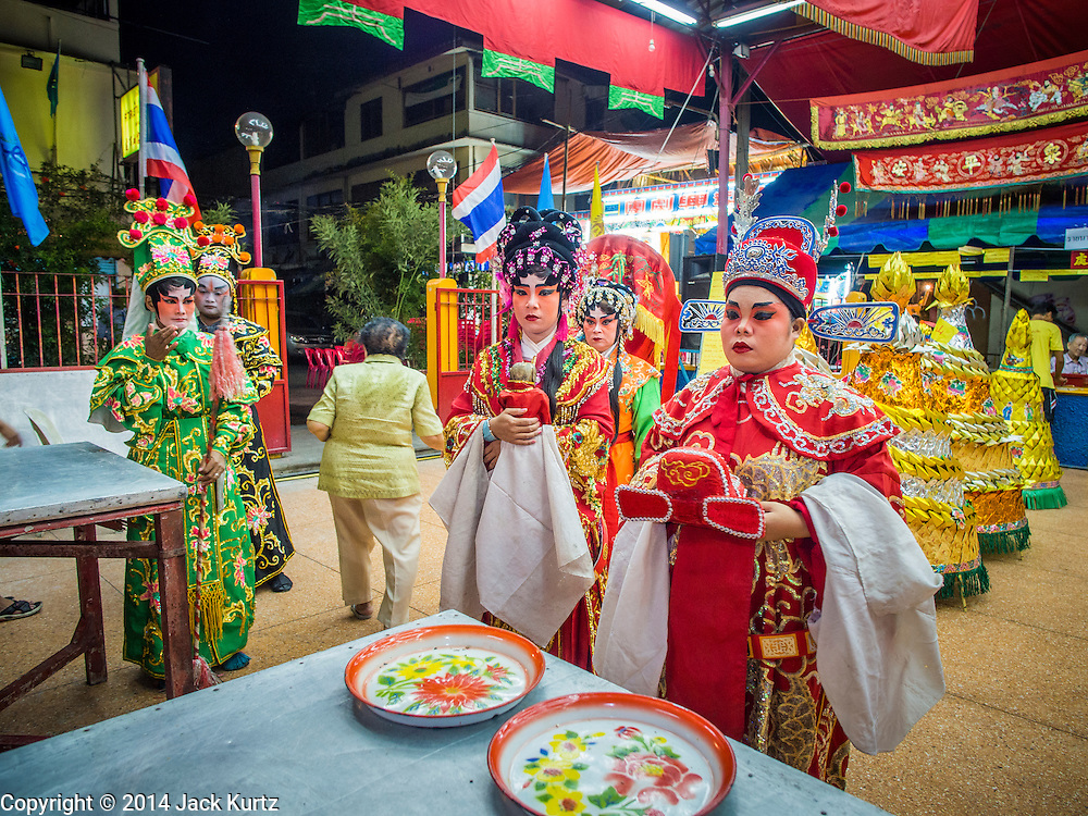 """18 AUGUST 2014 - BANGKOK, THAILAND:   Members of the Lehigh Leng Kaitoung Opera troupe pray in the shrine at the beginning of a performance at Chaomae Thapthim Shrine, a small Chinese shrine in a working class neighborhood of Bangkok. The performance was for Ghost Month. Chinese opera was once very popular in Thailand, where it is called """"Ngiew."""" It is usually performed in the Teochew language. Millions of Chinese emigrated to Thailand (then Siam) in the 18th and 19th centuries and brought their culture with them. Recently the popularity of ngiew has faded as people turn to performances of opera on DVD or movies. There are still as many 30 Chinese opera troupes left in Bangkok and its environs. They are especially busy during Chinese New Year and Chinese holiday when they travel from Chinese temple to Chinese temple performing on stages they put up in streets near the temple, sometimes sleeping on hammocks they sling under their stage. Most of the Chinese operas from Bangkok travel to Malaysia for Ghost Month, leaving just a few to perform in Bangkok.      PHOTO BY JACK KURTZ"""