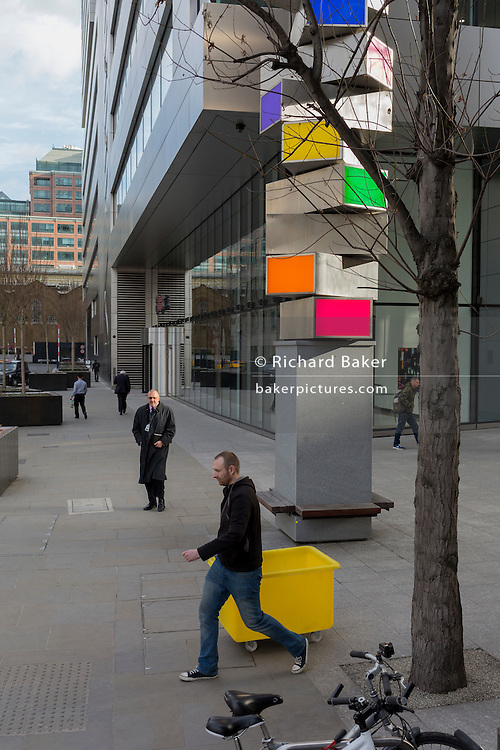 A contractor with a yellow bin passes underneath a column of coloured panels within a landscape of corporate office space of modern architecture, on 16th February 2017, in the City of London, England.