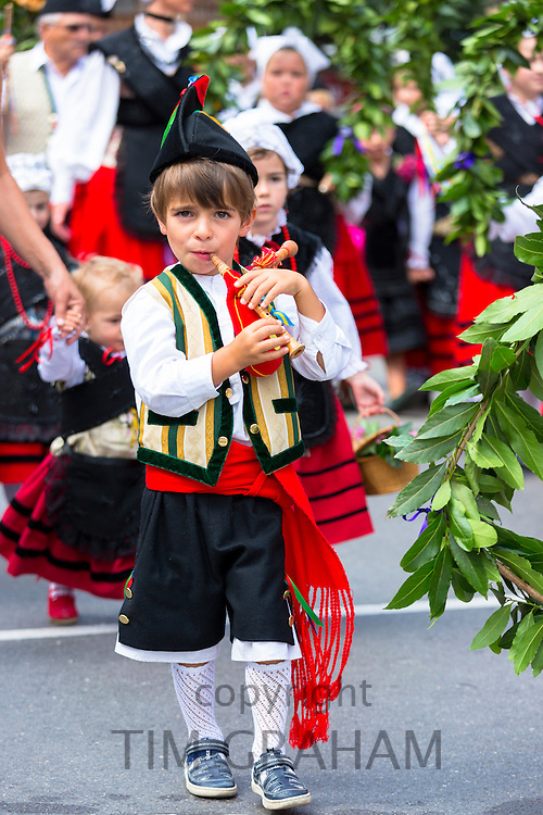 Spanish boy playing musical instrument at traditional fiesta at Villaviciosa in Asturias, Northern Spain