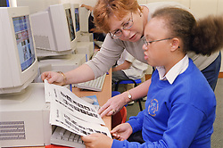 Female teacher helping primary school girl to use computer in information technology lesson,