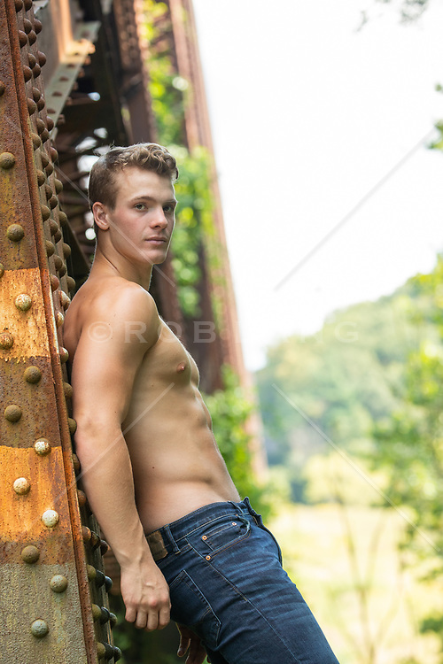 sexy shirtless man leaning against a train trestle