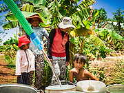03 JUNE 2016 - SIEM REAP, CAMBODIA:  Villagers watch as their water jugs are filled at a water distribution point in Sot Nikum, a village northeast of Siem Reap. Wells in the village have been dry for more than three months because of the drought that is gripping most of Southeast Asia. People in the community rely on water they have to buy from water sellers or water brought in by NGOs. They were waiting for water brought in by truck from Siem Reap by Water on Wheels, a NGO in Siem Reap. Cambodia is in the second year of  a record shattering drought, brought on by climate change and the El Niño weather pattern. There is no water to irrigate the farm fields and many of the wells in the area have run dry.     PHOTO BY JACK KURTZ