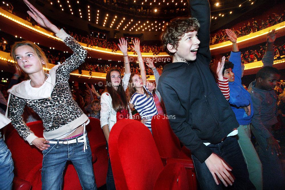 Nederland, Amsterdam , 20 december 2011..kindermatinee van de Notenkraker in het Muziektheater..1300 kinderen uit groep 5 & 6 (7 tm 9 jaar) uit heel Amsterdam (echt.uit alle stadsdelen zo'n beetje) komen naar een speciale ingekorte versie.kijken van de Notenkraker onder begeleiding van 45 onderwijsassistenten.van het ROC. In de pauze doen alle leerlingen nog een dansje in de zaal.(rond 14.50 ongeveer) onder begeleiding van 3 dansers..VOORKEURSFOTO!.Foto:Jean-Pierre Jans