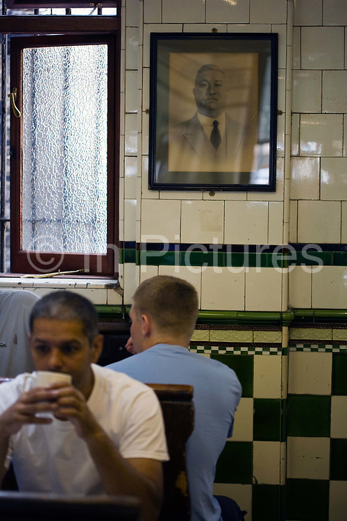 Customers in Manze's Eel, Pie and Mash shop on Tower Bridge Road London beneath a portrait of Michael Manze the restaurant's founder.This pie shop was opened in 1897 and is the oldest pie and eel shop in the countryEel, pie and mash shops are a traditional but dying business. Changing tastes and the scarcity of the eel has meant that the number of shops selling this traditional working class food has declined to just a handful mostly in east London. The shops were originally owned by one or two families with the earliest recorded, Manze's on Tower Bridge Road being the oldest surviving dating from 1908. Generally eels are sold cold and jellied and the meat pie and mash potato covered in a green sauce called liquor.