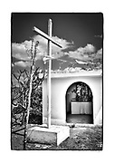 SHOT 2/19/19 12:33:19 PM - A cross and a Virgin of Guadalupe statue stands watch over prayer candles inside a roadside capilla near Bolonchén, Mexico. Bolonchén or Bolonchén de Rejón is a town in the Mexican state of Campeche, about 120 km East from the state capital, Campeche, in Hopelchén Municipality. As of 2010 the town had a population of 3,975 people. The capillas are often dedicated to certain patron saints or the memory of someone that has died at or near the site. Common throughout the backroads and secondary highways of Mexico they often contain prayer candles, pictures, personal artifacts or handwritten notes. (Photo by Marc Piscotty / © 2019)