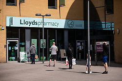 © Licensed to London News Pictures .  07/05/2020 . Salford, UK. People queue at 2 meters' distance from one another , outside Lloyds Pharmacy at Salford Gateway Centre on Broadwalk in Salford . Photo credit : Joel Goodman/LNP