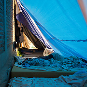 """A burundian university student seeking shelter outside the US embassy in Bujumbura, takes a nap in a improvised tent. The students moved to the area in early May because, they claim, the US authorities ensure their security, after their university was closed amid anti-government protests. The government closed the university at the end of April, citing """"insecurity""""."""