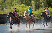 Riders ride theor horses through a river at the Heart Six Ranch, Wyoming