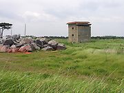 Wartime look out tower and pile of igneous boulders ready for use in coastal defence engineering project. Concept of two types of defence on the East Anglian coast. East Lane, Bawdsey, Suffolk, England