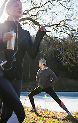 Woman jogging while man is stretching on fitness trail in front of frozen lake