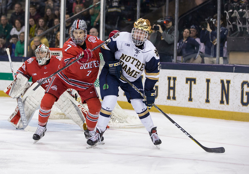 March 17, 2018:  Notre Dame forward Cam Morrison (26) and Ohio State defenseman Wyatt Ege (7) battle in front of the net during NCAA Hockey game action between the Notre Dame Fighting Irish and the Ohio State Buckeyes at Compton Family Ice Arena in South Bend, Indiana.  Notre Dame defeated Ohio State 3-2 in overtime.  John Mersits/CSM