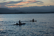 Two men on their way to catch fish paddle in outrigger canoes at sunset near Kranket Island in Madang, Papua New Guinea.  (August 2017)