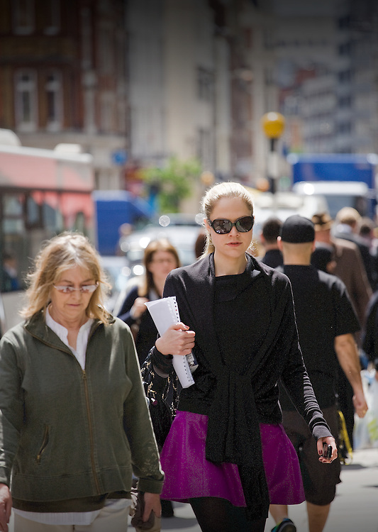 tall blonde business women walking along pavement in Mayfair wearing sunglasses and holding some documents