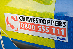 Crimestoppers sign on the side of a police car,