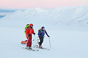 Michelle Blade (left) and Mylène Jacquemart ski across Breinosa, Svalbard, above Adventadlen, at dawn.