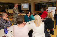 Staff Sgt. Rick Frost of the NH National Guard counterdrug task force (standing) checks in on the table discussion with Mayor Ed Engler and local participants. Christine Gingerella writes contacts to begin building a community coalition addressing drug abuse in the city at Laconia Middle School Thursday evening.   (Karen Bobotas/for the Laconia Daily Sun)