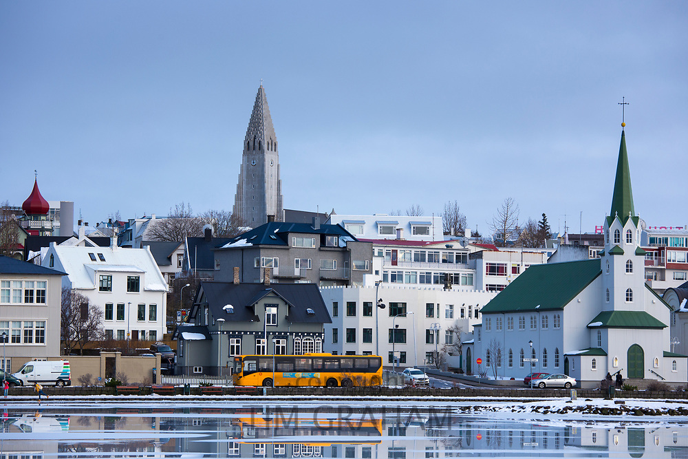 Yellow bus - coach - in the capital city of Reykjavik and Lutheran church Hallgrímskirkja Cathedral, Iceland