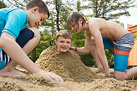 Bradley and Ryan bury their friend Jason in the sand at Ellacoya State Beach on Friday.  (Karen Bobotas/for the Laconia Daily Sun)