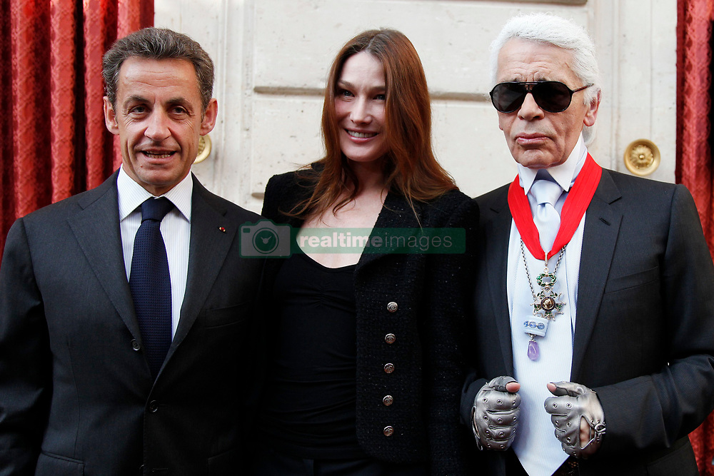 German designer Karl Lagerfeld (R) wears the Commander's Cross of the Legion of Honour (Croix de Commander de la Legion d'Honneur) he received from France's President Nicolas Sarkozy (L) as Carla Bruni-Sarkozy (C) looks on at a ceremony at the Elysee Palace in Paris, France on June 3, 2010. Photo by Jacky Naegelen/Pool/ABACAPRESS.COM