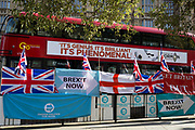 On the day that the EU in Brussels agreed in principle to extend Brexit until 31st January 2020 (aka 'Flextension') and not 31st October 2019, a London bus featuring an ad for the Book od Mormon, drives past Brexit Party flags and banners during a Brexit protest outside parliament, on 28th October 2019, in Westminster, London, England.