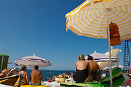 Sunbathers sitting on sun beads looking at the sea. Piran , Slovenia Visit our PHOTO COLLECTIONS OF SLOVANIAN  HISTOIC PLACES for more photos to download or buy as wall art prints https://funkystock.photoshelter.com/gallery-collection/Pictures-Images-of-Slovenia-Photos-of-Slovenian-Historic-Landmark-Sites/C0000_BlKhcYWnT4Sites/C0000qxA2zGFjd_k